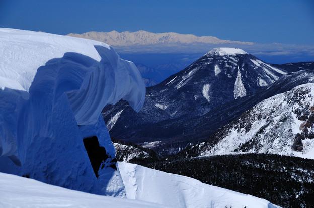 遠く白馬三山。手前蓼科山。間近に崩落寸前の雪庇